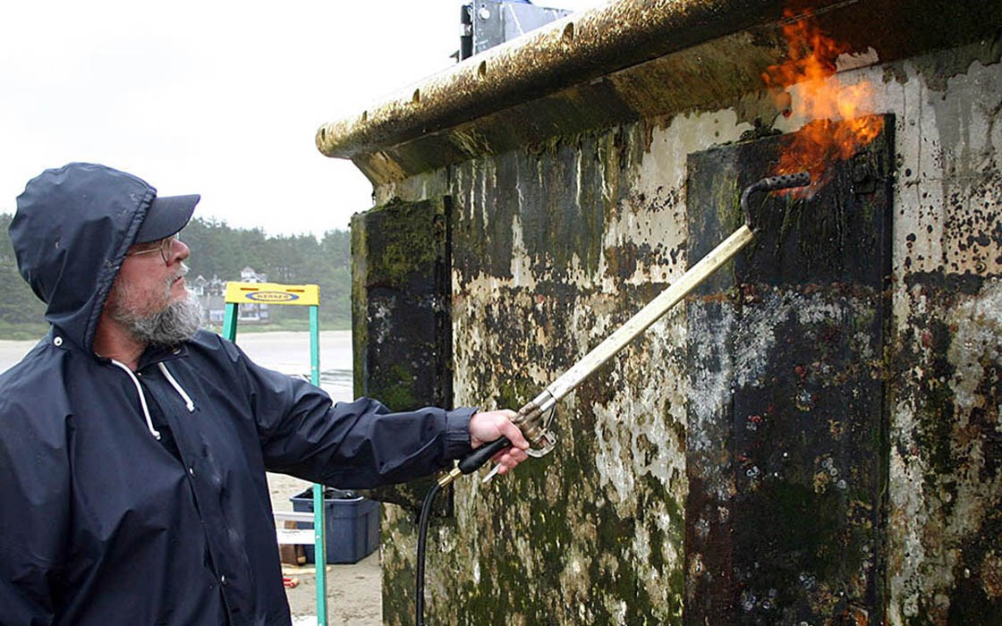 The structure was scraped clean then, low-pressure torches were used to sterilize the dock. All removed material was bagged, hauled up the beach well above the high tide line and stored temporarily. Agate Beach, Oregon, USA. June 2012.
