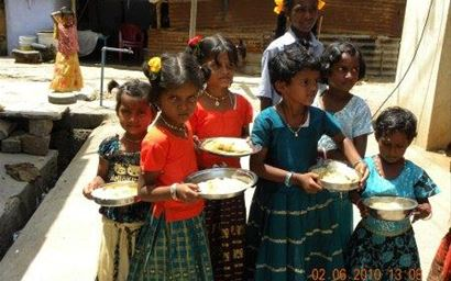 Children are getting served with food under mid-day meal scheme, in India