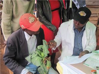 A plant doctor in Tanzania advising a farmer on his crop