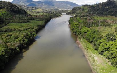 A wide river banked by green tropical forest with sky in the background