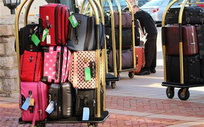 luggage and suitcases stacked up on bellman's cart