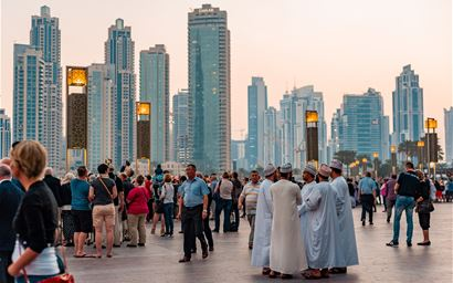 crowded side walk in Dubai. Men in traditional dress surrounded by tourists.