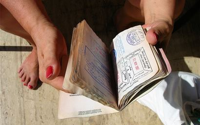 passport being held full of visa stamps from world travel