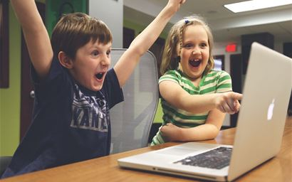 excited children playing on laptop computer