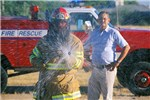 Northwest Fire District's Captain John Estes of Tucson, Arizona, uses a wide spray of water and chemical wetting agent as a means of subduing Africanized honey bees. Looking on is ARS entomologist Eric Erickson, who taught this control method to fire departments throughout Arizona.