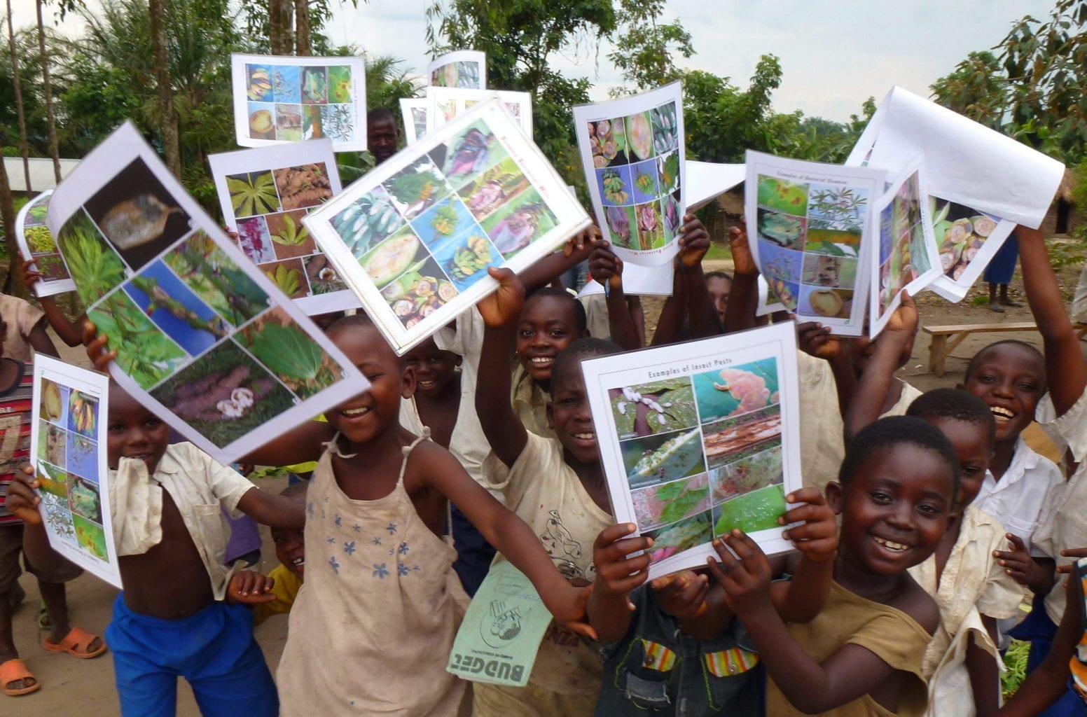 Village children showing poster on invasive pests