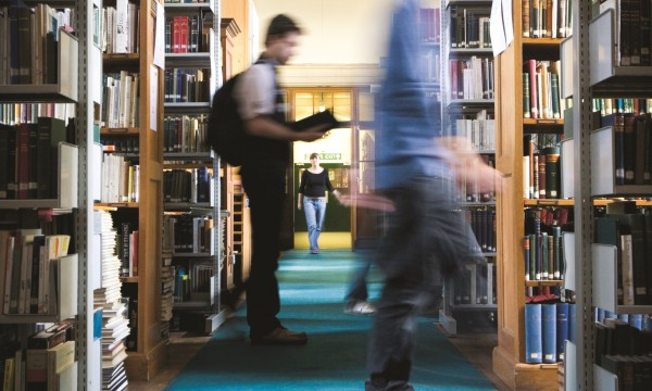 Blurred image of people walking between shelves in a library