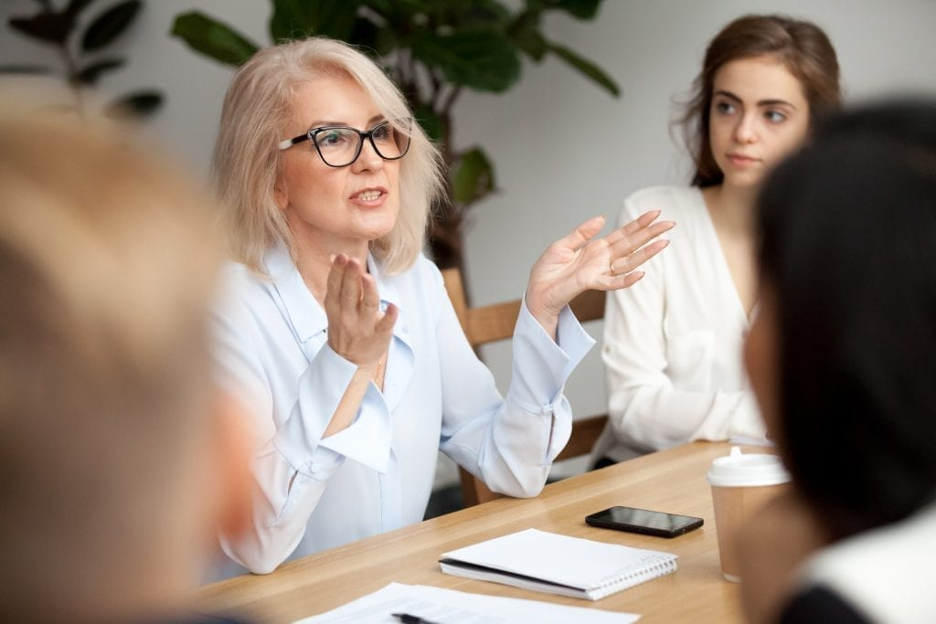 White haired lady talking to group of students